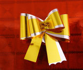 Golden ribbon on red — Stock Photo