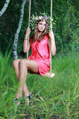 Young beauty girl on swing outdoors — Stock Photo
