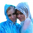 Two girls in raincoats - Stock Photo