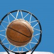 Basketball in the net against clear blue skies — Stock Photo