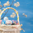 Happy Easter-text on a hand painted egg in a basket — Stock Photo