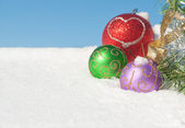 Colorful Christmas ornaments in snow — Stock Photo