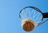 Basketball in net agaisnt blue skies — 图库照片