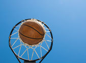 Basketball in net agaisnt blue skies — Stock Photo