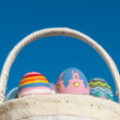Basketful of colorful hand painted Easter eggs against blue sky — Stock Photo