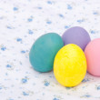 Pastel colored hand painted Easter eggs on a white cloth — Stock Photo #5559708