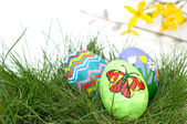 Colorful hand painted Easter eggs in green spring grass — Stock Photo
