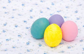 Pastel colored hand painted Easter eggs on a white cloth — Stock Photo