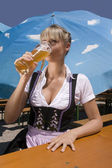 Young woman in traditional costume in the beer garden — Stock Photo