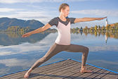 Young woman doing yoga by the lake — Stock Photo