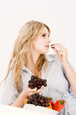 Beautiful young woman eating fruit in — Stock Photo