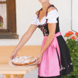 Young woman in dirndl with cake — Stock Photo