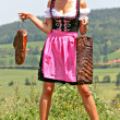 Royalty-Free Stock Photo: Young woman in dirndl with bacon