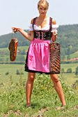 Young woman in dirndl with bacon — Stock Photo
