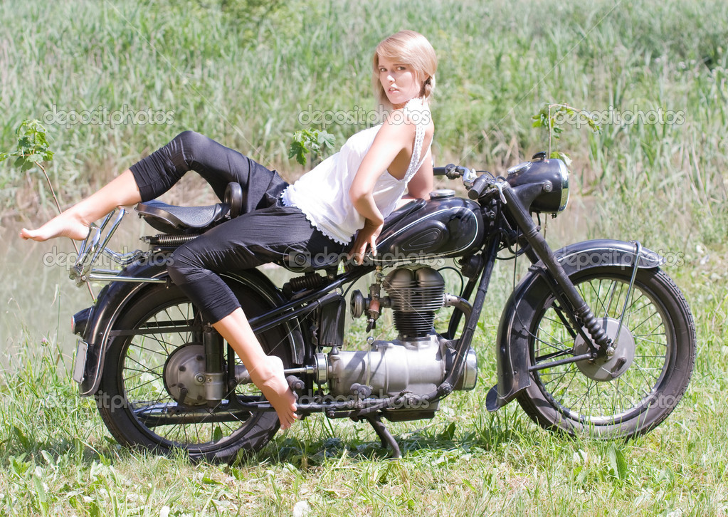 Fashionably dressed woman seated on an old motorcycle — Stock Photo #6454498