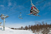 Chair lift with skiers on a blue sky — Stock Photo