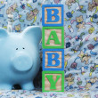 Stock Photo: Baby with Blue Piggy Bank