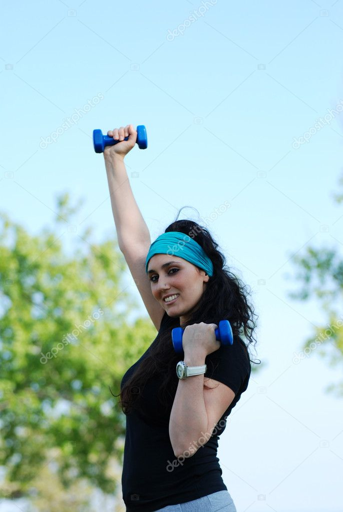 Beautiful young woman training with weights outdoor  Stock Photo #5621012