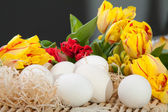 Yellow and red tulips with white eggs lying on a straw tray — Stock Photo