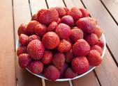 Ripe fresh strawberry on a white plate on a wooden table — Stock Photo