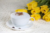 Cup of coffee on a white saucer and on the background yellow flo — Stock Photo