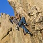 Постер, плакат: Rock climber dangling