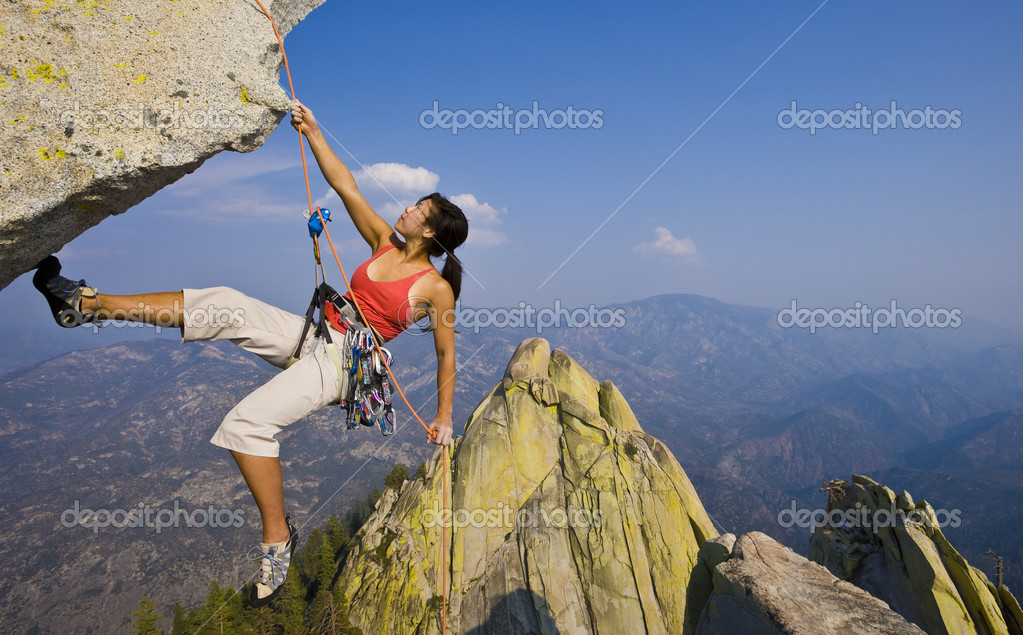 Female climber rappelling from the summit of an overhanging cliff. — Stock Photo #5543762