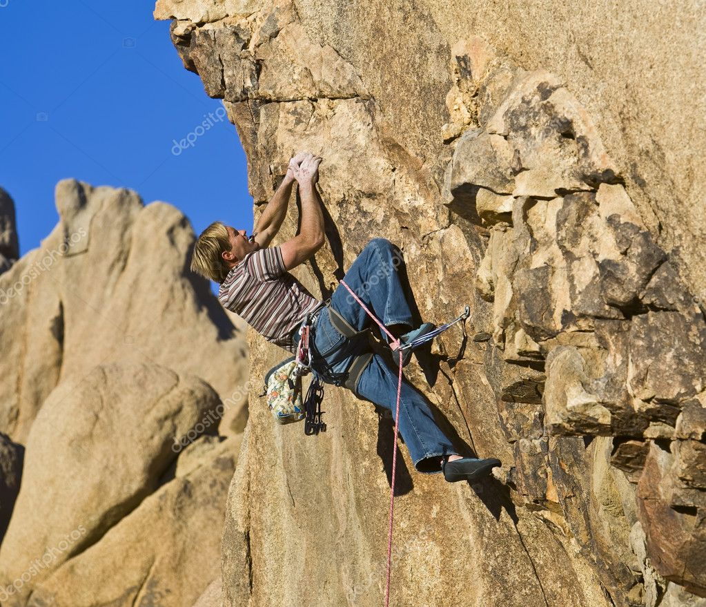A rock climber clings to an overhanging rock face. — Stock Photo #5546249