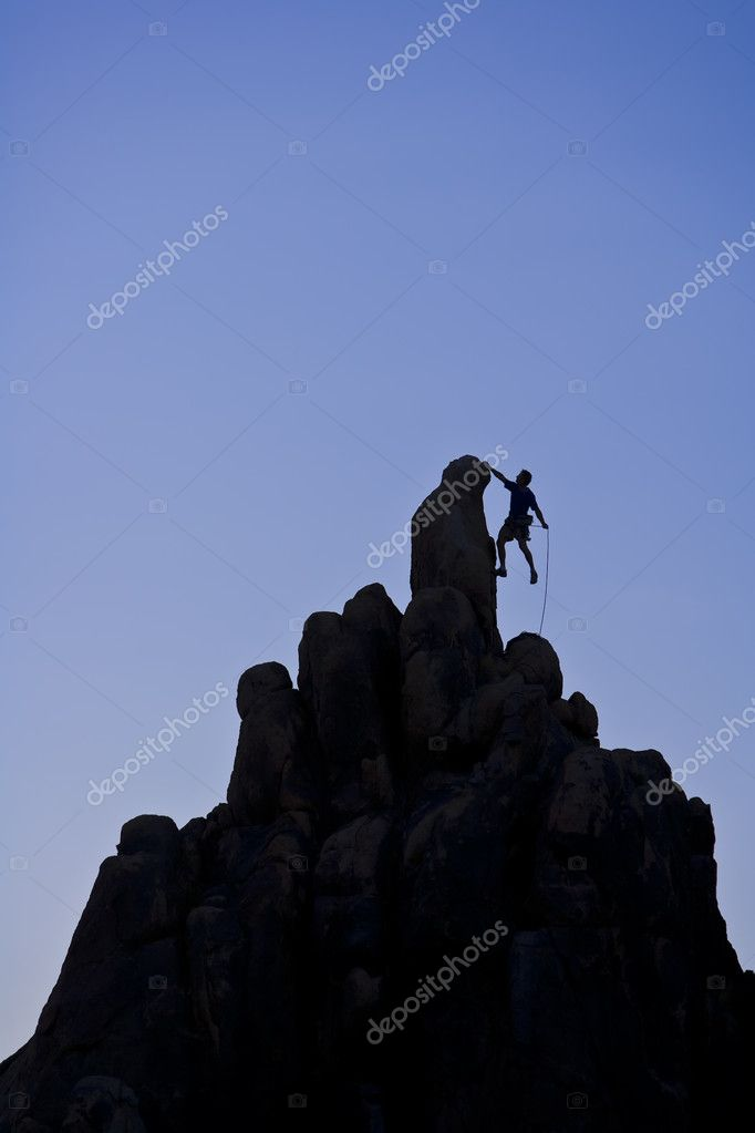 A climber is silhouetted summitting a rock spire in the Sierra Nevada mountains. — Stock Photo #5546260
