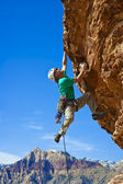 Male rock climber reaching for the summit. — Stock Photo