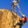 Stock Photo: Rock climbing team reaching summit.