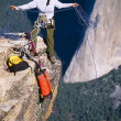 Rock climbing team reaching the summit. - Stock Photo
