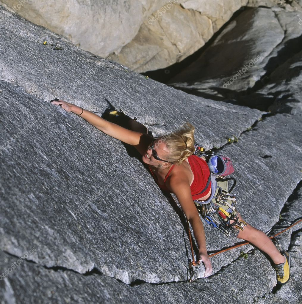 Female climber stretches for her next hold on a challenging route at Suicide Rock, in Idyllwild, California, on a sunny day.  Stock Photo #5586075