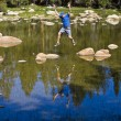 Rock hopping across an alpine lake - Foto Stock