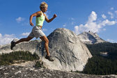 Female trail runner jumping. — Stock Photo