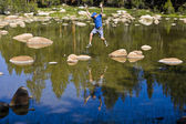 Rock hopping across an alpine lake — Stock Photo