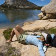 Female hiker relaxing near a lake. — Stock Photo