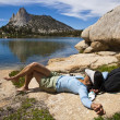 Stock Photo: Female hiker relaxing near a lake.