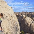 Female rock climber clinging to a cliff. — Stock Photo