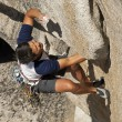 Rock climber clinging to steep cliff. — Stock Photo