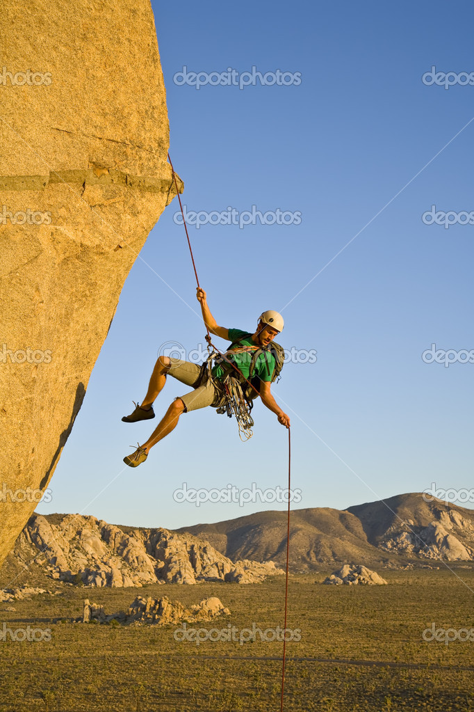 A rock climber rappelling past an overhang in Joshua Tree National Park, California, on a summer evening. — Stock Photo #5647114