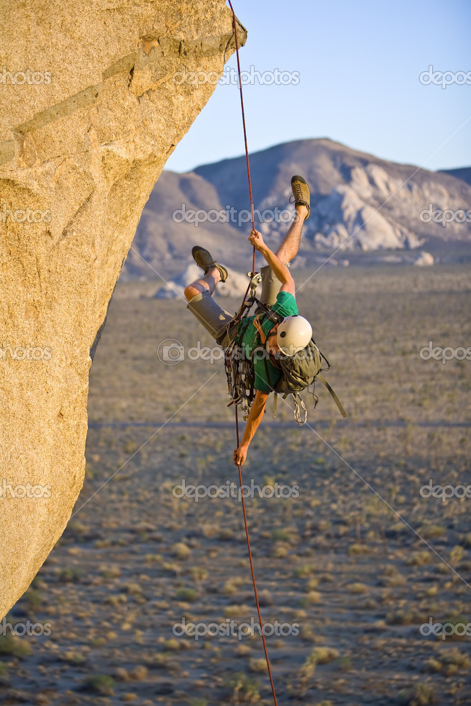 A rock climber rappelling past an overhang in Joshua Tree National Park, California, on a summer evening. — Stock Photo #5647165