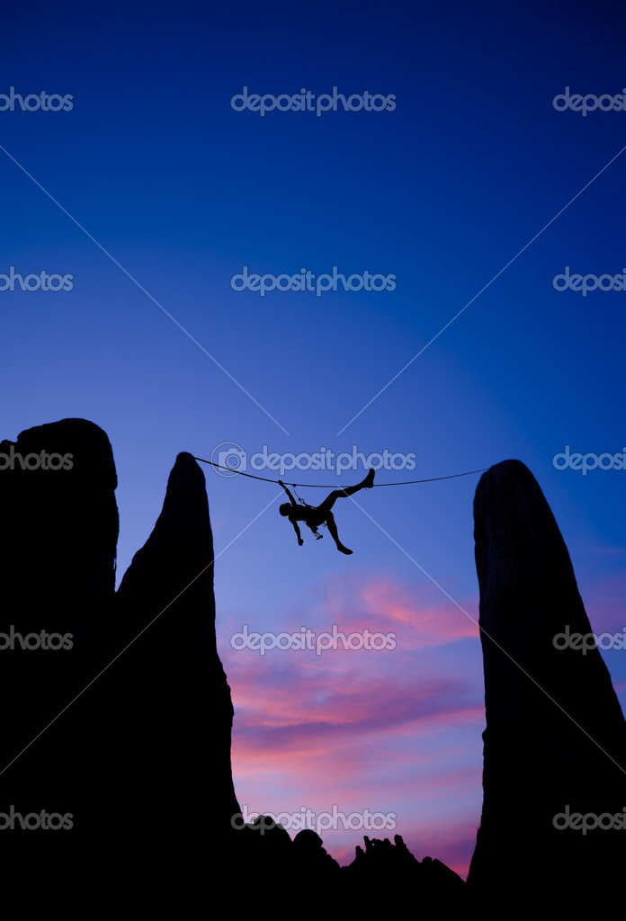 A climber is silhouetted as she pulls herself across a gap between two pinnacles, in the Sierra Nevada  Mountains, California. — Stock Photo #5648274