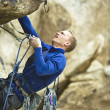 Rock climber clinging to a cliff. - Stock Photo