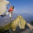 Stock Photo: Female rock climber rappelling.