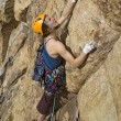 Female rock climber clinging to a crack. — Stock fotografie