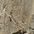 Tema of climbers ascending a steep rock face — Stock Photo