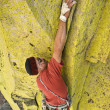 Male climber working his way up a steep crack. - Stock Photo