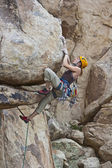 Rock climber clinging to a steep cliff. — Stock Photo