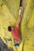 Male climber working his way up a steep crack. — Stock Photo